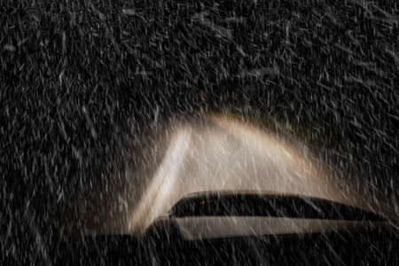 Driving a car at night in a snowstorm Imagens
