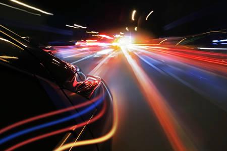 Auto versnellen in de nacht met neonlicht Stockfoto