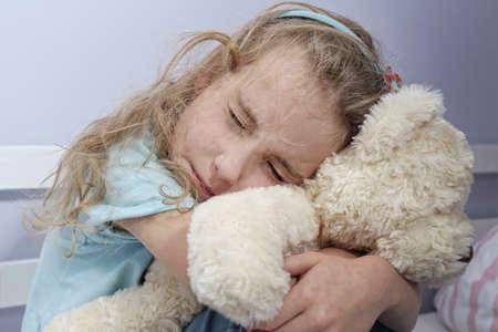 psicologia infantil: muchacha triste sola que se sienta en la sala abrazando osito