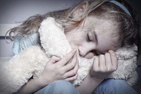 pedophilia: Crying young girl hugging teddy Stock Photo