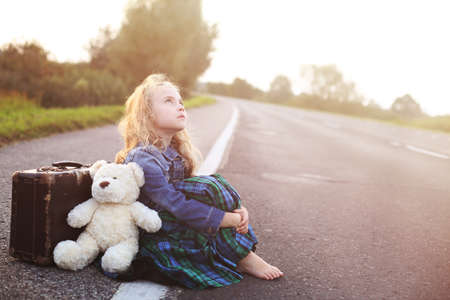 angry teddy: Orphan sits alone on the road with a suitcase