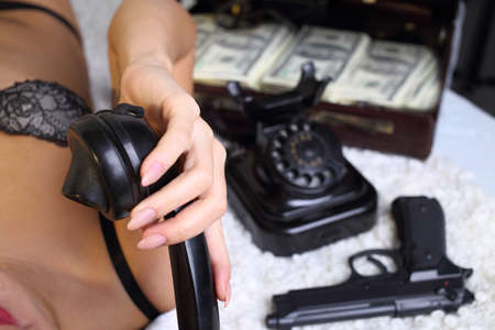sexy woman with a suitcase of money talking on the phone photo