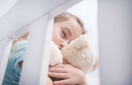 angry teddy: Sad young girl hugging a teddy bear in a child