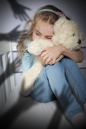 Bullying frightened child hugging a teddy bear Stock Photo