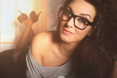 lonley: sensual beautiful woman lying on a bed with glasses