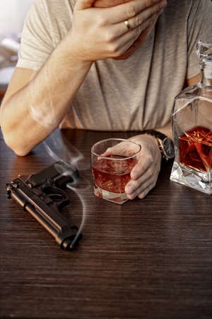 devastated: Devastated man with a gun and alcohol Stock Photo