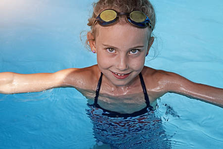 private schools: Youthful girl swimming in a pool Stock Photo