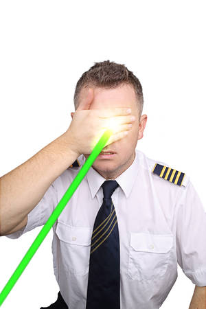 blinded: The pilot on a white background blinded by laser