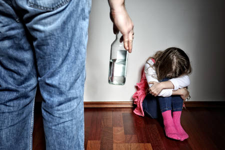 abuse: Father with belt stands above the frightened daughter