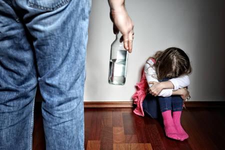 Vader met riem staat boven de bange dochter Stockfoto