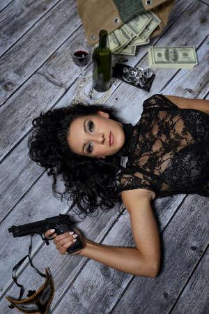 scruples: Young girl with a gun money and a bottle of wine Stock Photo