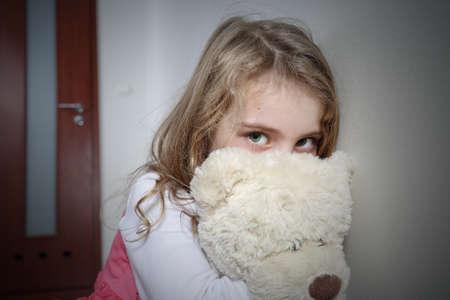 psicologia infantil: Muchacha triste joven abrazando a un oso de peluche Foto de archivo