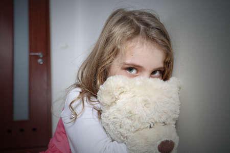pedophilia: Young sad girl hugging a teddy bear
