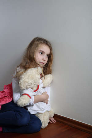 apathy: introverted child sitting with teddy bear