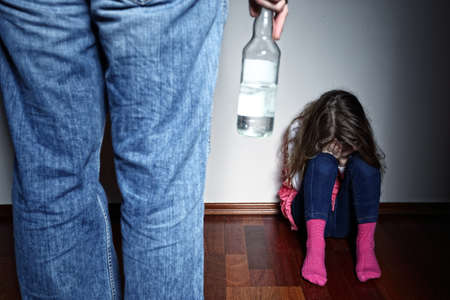 Drunk father standing over a crying daughter photo