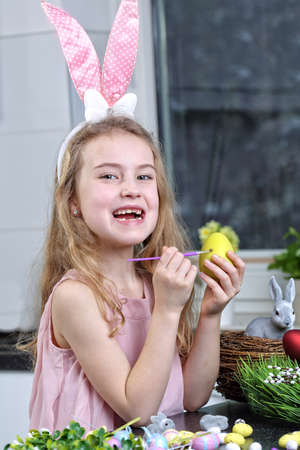 young girl in bunny ears painting Easter egg photo