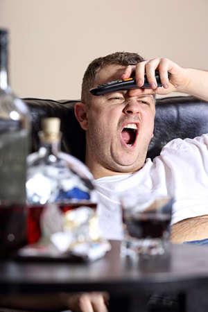 A man yawns watching TV photo