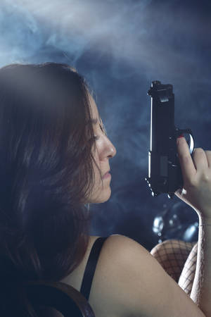 war crimes: Enigmatic and mysterious woman with gun Stock Photo