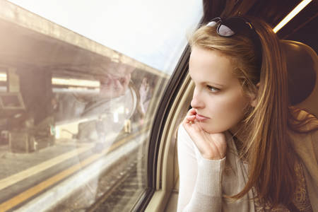 railway transportation: Pensive young girl on the train at the station