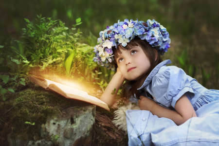 Reading fairy tales by a little girl in a meadow Archivio Fotografico