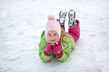 antics: Cheerful young girl lying in the snow