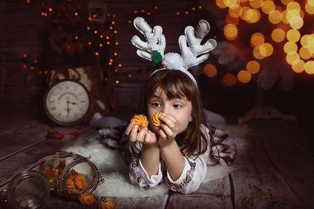 A girl waiting for santa eats cookies photo