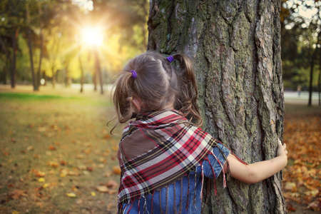 exceptionally: Young girl hugging a tree on a sunny day