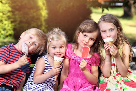 eating ice cream: adorables niños que comen el helado en vacaciones