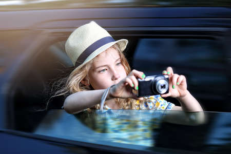 season photos: Fascinated young girl artist takes pictures while driving Stock Photo