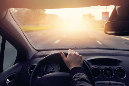 steering: The road to success - a driver traveling on a road to the sun