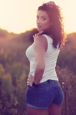 pantalones cortos: Hermosa chica en pantalones cortos posando en el prado en día de verano
