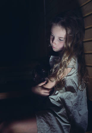 lost child: A sad little girl hugging a doll at home