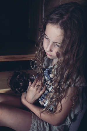 girl doll: Domestic violence - a girl hugging a doll Stock Photo