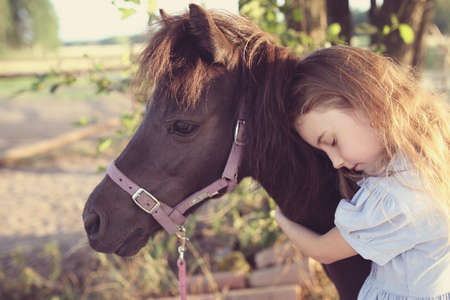 Young girl hugs a pony on a farm