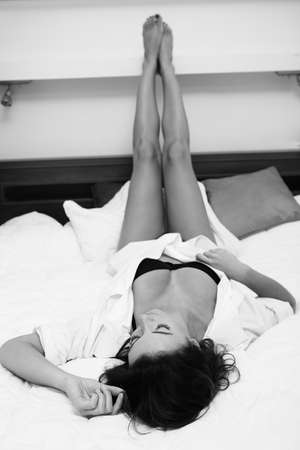 mujer en la cama: Una mujer hermosa en una camisa y el sujetador acostado en la cama