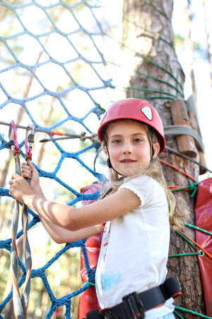 cuteness: Agile girl travels the trail rope park Stock Photo