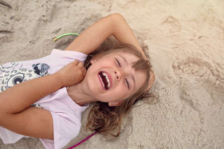 Happy little girl laughing on the beach Stock Photo