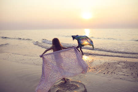 Two young girls run with scarves on the beach