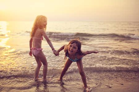 Dos chicas jóvenes que juegan en la playa