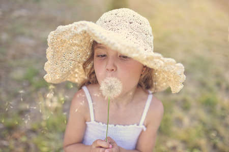 dandelion: Young girl in a hat blowing dandelion Stock Photo