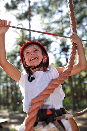 niño trepando: Chica joven en el parque de cuerdas Foto de archivo