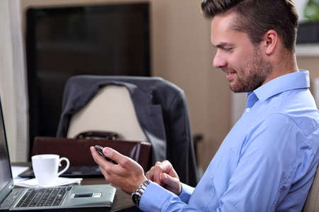 telecommuting: Young businessman checks the messages on the phone at home Stock Photo