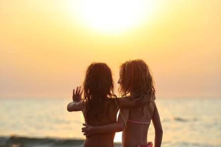 amistad: Dos niñas menores miran al atardecer