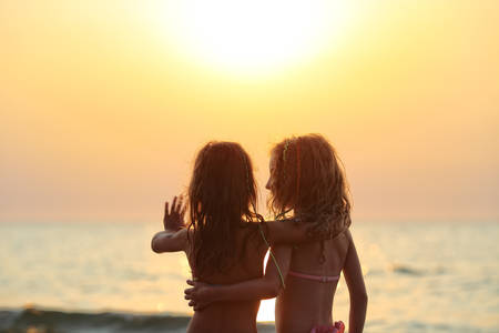 friendship: Two juvenile girls stare at sunset Stock Photo