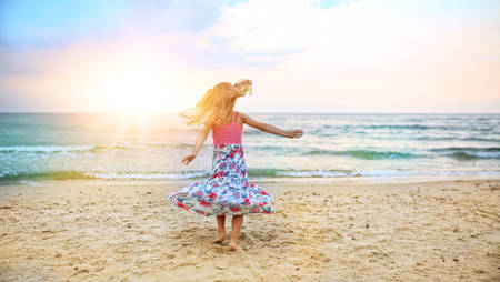 baby in hands: carefree girl dancing on the beach in a dress