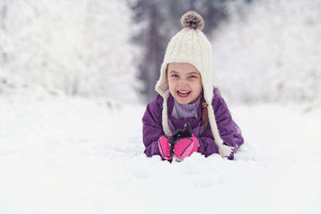 family playing: Joyful child lies on the snow Stock Photo