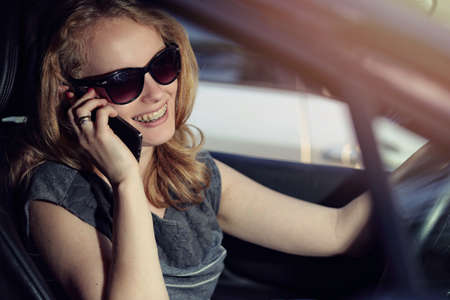 lady on phone: Woman talking on the phone in the car