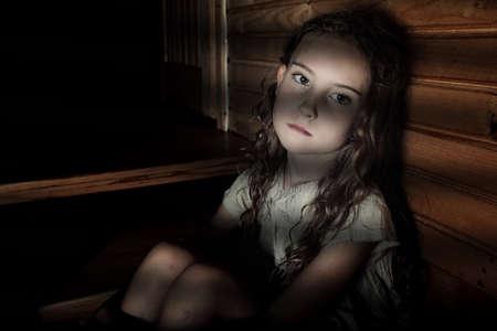 Chica deprimida que se sienta en un pasillo oscuro en el hogar Foto de archivo
