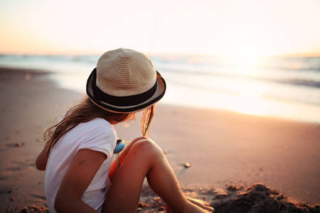 relaxing beach: girl in a hat sitting on the seashore