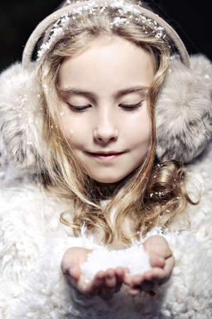 Earmuffs: The girl in fur earmuffs in winter evening Stock Photo